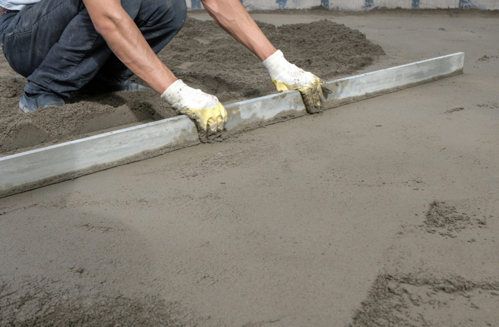 Construction worker using a tool to smooth out fresh concrete
